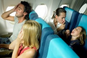 girl-5-7-yelling-behind-young-couple-in-airplane